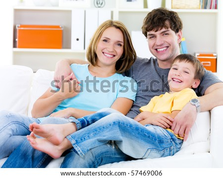 Beautiful young happy family with son sitting on the sofa - indoors