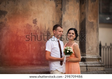 beautiful young happy stylish caucasian bride and groom on the background impressive architecture, Lviv, summer
