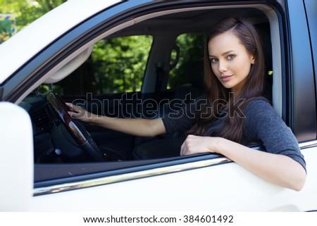 Beautiful young happy woman in car. Attractive  caucasian girl sitting in white auto. pretty female person driving big car suv - stock photo