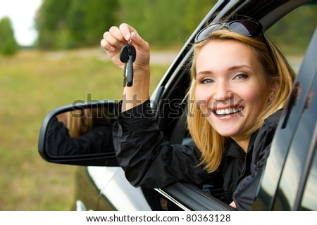 Beautiful young happy woman in  car showing the keys - outdoors - stock photo