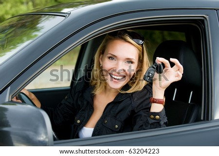 Beautiful young happy woman in the new car with keys - outdoors - stock photo