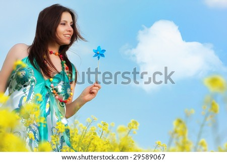 beautiful young happy woman on rapeseed field in bloom - stock photo