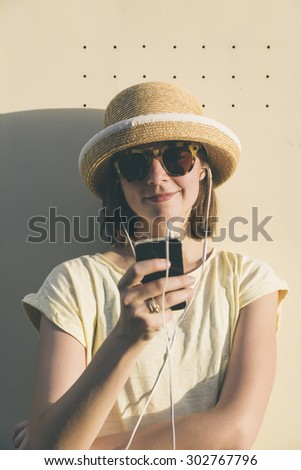 Beautiful young hipster Caucasian woman with smartphone and earphones, texting and listening to music. Happy teenage girl with blonde hair wearing a hat. - stock photo