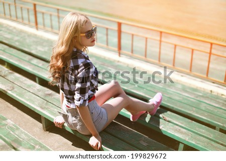 Beautiful young hipster girl sitting on the bench looking away - stock photo