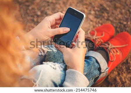 Beautiful young  hipster woman using smart phone at beach - stock photo