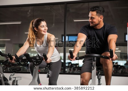 Beautiful young Hispanic woman flirting and talking to a guy while they both do some spinning at a gym. Focus on woman - stock photo