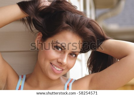 beautiful young hispanic woman playing with her long hair - stock photo