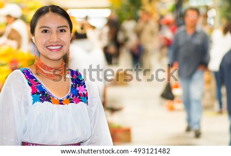 Beautiful young hispanic woman wearing andean traditional blouse posing for camera inside fruit market, colorful healthy food selection in background