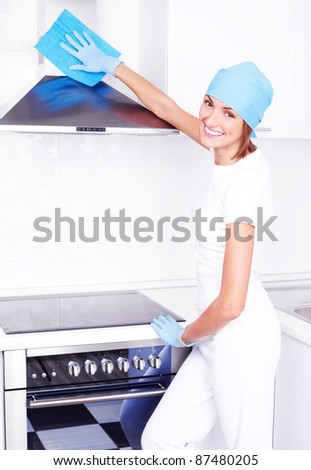 beautiful young housewife cleaning the kitchen hood at home - stock photo