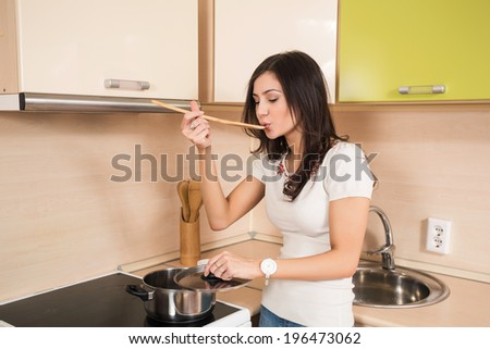 Beautiful young housewife in the kitchen