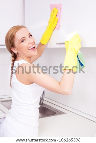 beautiful  young housewife wearing gloves and holding detergent, cleaning the furniture  in the kitchen at home