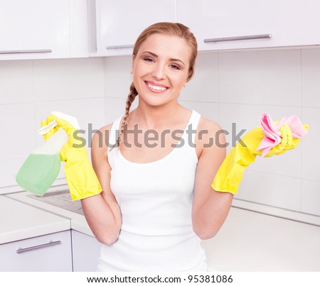 beautiful  young housewife wearing gloves and holding detergent,  in the kitchen at home - stock photo