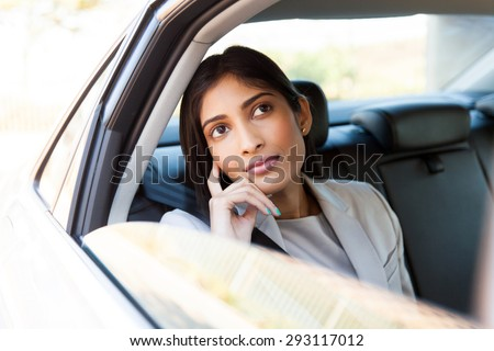 beautiful young indian businesswoman in a taxi - stock photo
