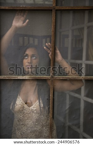 Beautiful young Indian woman in an attractive nightie looking out old, battered screen door. - stock photo