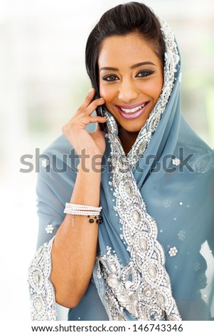 beautiful young Indian woman in traditional clothing talking on cellphone - stock photo