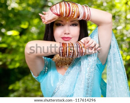 Beautiful young indian woman in traditional clothing with bridal makeup and jewelry. gorgeous brunette bride traditionally dressed Outdoors in India. Girl bollywood dancer in Sari. Arabian bellydancer - stock photo