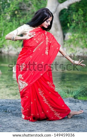 Beautiful young indian woman in traditional clothing with bridal makeup and jewelry. gorgeous brunette bride traditionally dressed in India. Girl bollywood dancer in Sari and henna on hands - stock photo