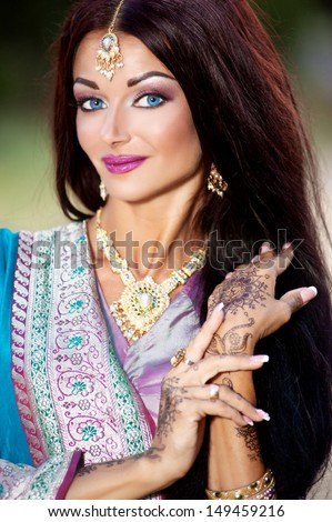 Beautiful young indian woman in traditional clothing with bridal makeup and jewelry. gorgeous  bride traditionally dressed in India. Girl bollywood dancer in Sari - stock photo