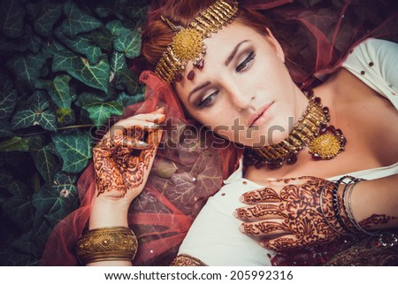 Beautiful young indian woman in traditional clothing with bridal makeup and jewelry. gorgeous brunette bride traditionally dressed Outdoors in India. Girl bollywood dancer in Sari and henna on hands - stock photo