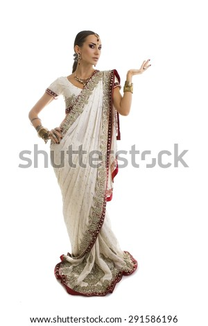 Beautiful Young Indian Woman in Traditional Clothing with Bridal Makeup and Oriental Jewelry. Beautiful Girl Bollywood dancer (Bellydancer) in Sari with open Hand palm.  - stock photo
