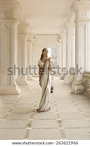 Beautiful young indian woman in traditional clothing with incense bridal makeup and oriental jewelry. Beautiful bollywood dancer in Sari posing in the eastern palace. Beautiful princess Girl praying - stock photo