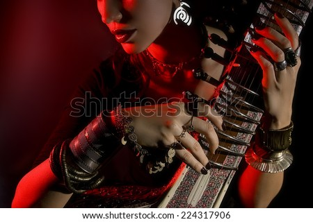 Beautiful young indian woman in traditional clothing with sitar and oriental jewelry. Beautiful bollywood Girl playing the sitar (red lens effect) - stock photo
