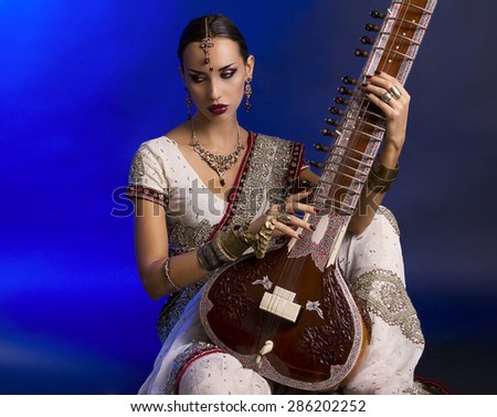 Beautiful Young Indian Woman in Traditional Sari Clothing with oriental jewelry, Bridal Makeup Playing the Sitar. Beautiful Bollywood Girl. Eastern fairy tale  (blue lens effect) - stock photo