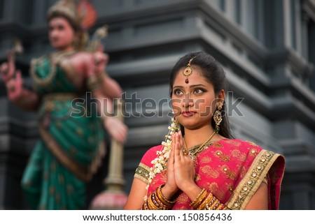 Beautiful young Indian woman in traditional sari dress praying in a hindu temple. - stock photo