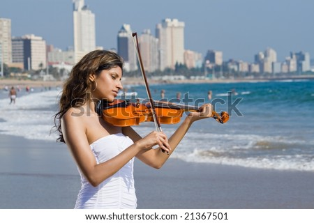 beautiful young indian woman play violin on beach - stock photo
