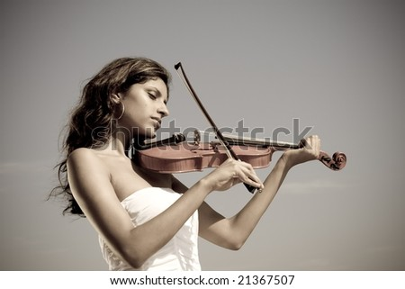 beautiful young indian woman play violin on beach