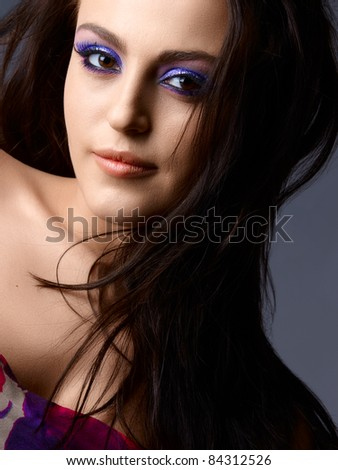 Beautiful young Italian woman with artistic purple eyeshadow and long hair looking with a soft smile - stock photo