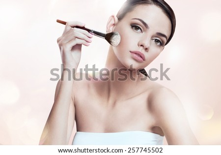 Beautiful young lady applying foundation on her face with tassel, skin care concept / photoset of attractive brunette girl on blurred beige background with bokeh   - stock photo