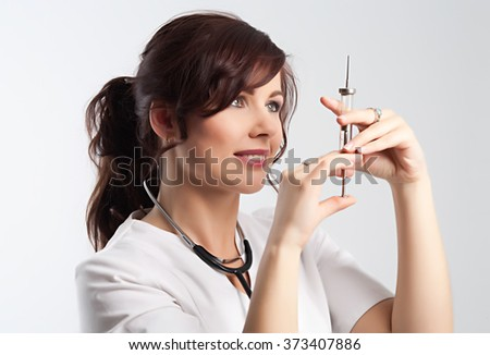 Beautiful young lady doctor with stethoscope and syringe preparing to make injection. Studio shoot. White background.