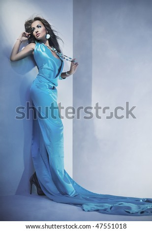 Beautiful young lady over romantic blue background - stock photo