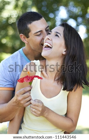 Beautiful young lady receives red flower from attractive young man - stock photo