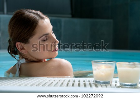 Beautiful young lady relaxing during a bath in a pool at thermal club - stock photo