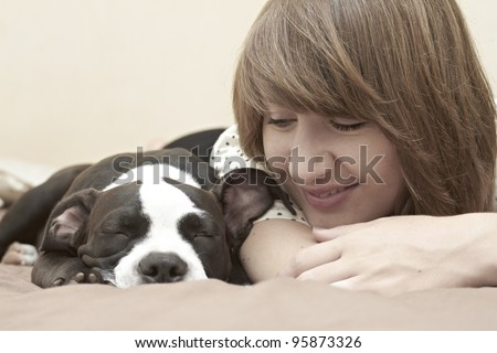 Beautiful young lady smiling at her Pit Bull puppy asleep on bed - stock photo