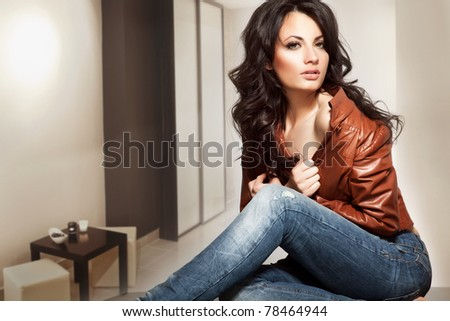 Beautiful young lady standing in a stylish interior - stock photo