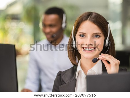 Beautiful young lady talking on headset at call center office. - stock photo