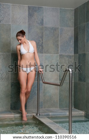 Beautiful young lady walking through water pools for kneipp treatment - stock photo