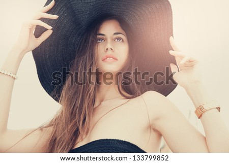 beautiful young lady with a Big black hat posing on a sunny day. Outdoors , Horizontal shot. - stock photo