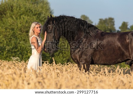 Beautiful young lady with black stallion. - stock photo