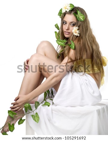 Beautiful young lady with flower and leaf  in her hair posing in studio - stock photo