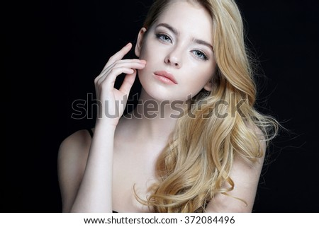 Beautiful young lady with make up face. Close-up of an attractive girl of European appearance on dark background. - stock photo