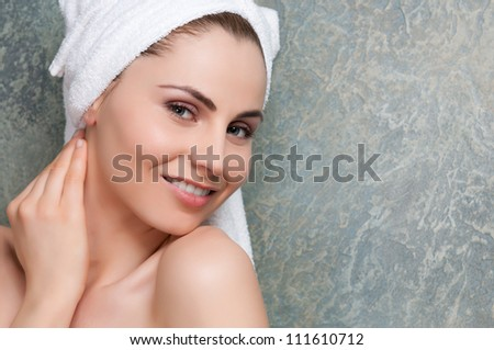 Beautiful young lady with towel smiling at spa