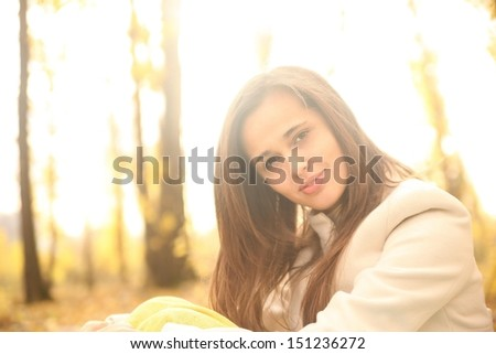 beautiful young latin hispanic brunette woman in yellow autumn park Copy space for inscription