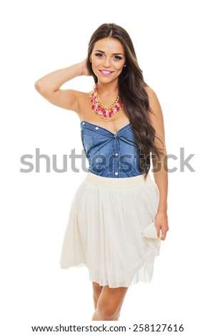 Beautiful young Latina woman with long brown hair in summer outfit. Gorgeous girl in blue denim and white tulle dress and fashionable necklace posing isolated on white background. Retouched. - stock photo