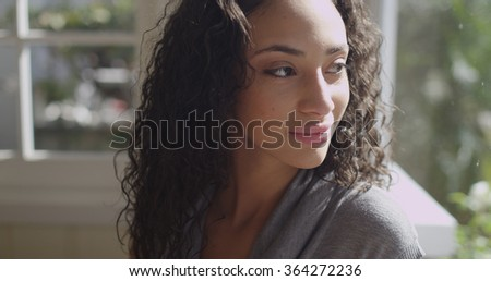 Beautiful young latino woman looking out a window. - stock photo