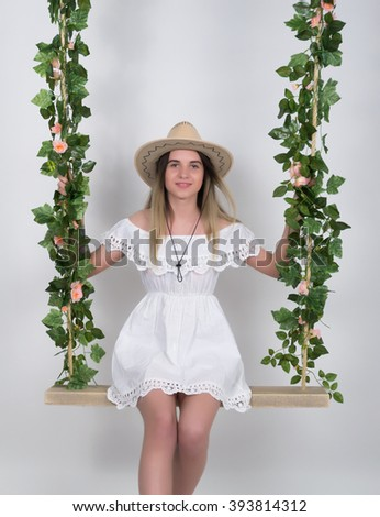 Beautiful young leggy blonde in a little white dress and white cowboy hat on a swing, wooden swing suspended from a rope hemp, rope wrapped vine and ivy - stock photo
