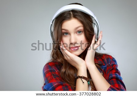 Beautiful young long-haired girl with headphones and telephone, listening music - stock photo